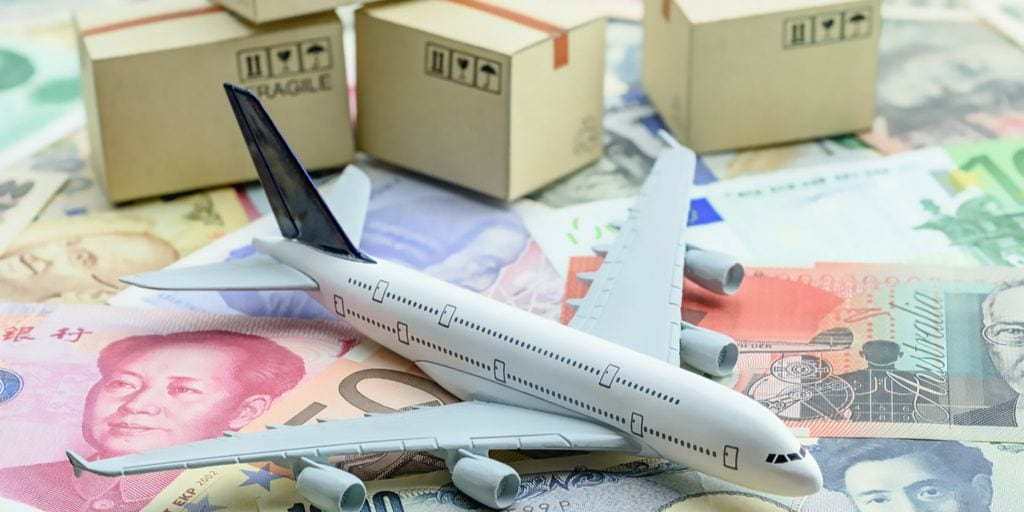 An Airplane On Top Of Money With Boxes In The Background Indicating Cross Border Shipping - Cedric Millar Tech Enabled Supply Chain Company Canada