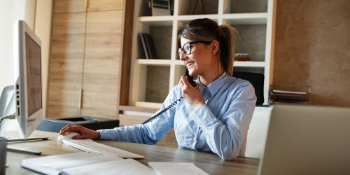 Businesswoman in her office.She sitting at the desk and talking on the phone.
