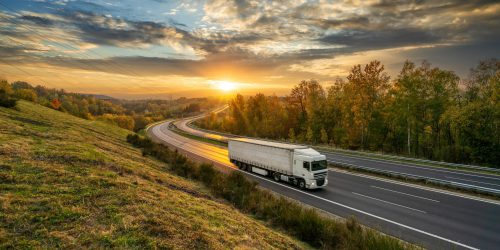 White truck driving on the asphalt highway in autumn landscape at golden sunset with dramatic clouds